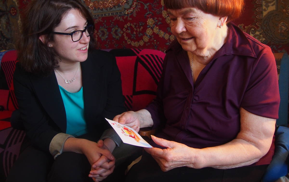 Beth Saffer handing a Rosh Hashanah card from a supporter to an older woman in Kiev Ukraine