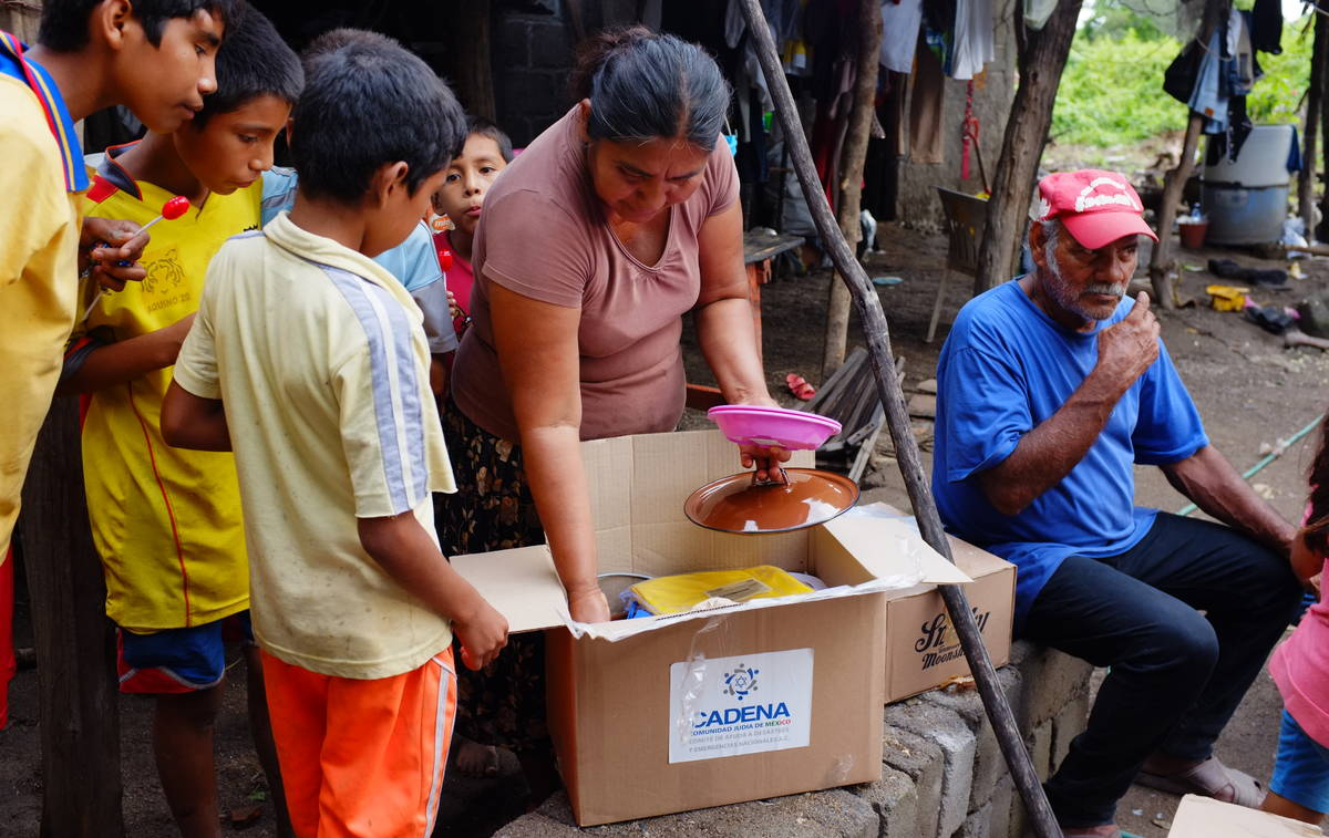 Dona Fausta opening box of needy supplies 4
